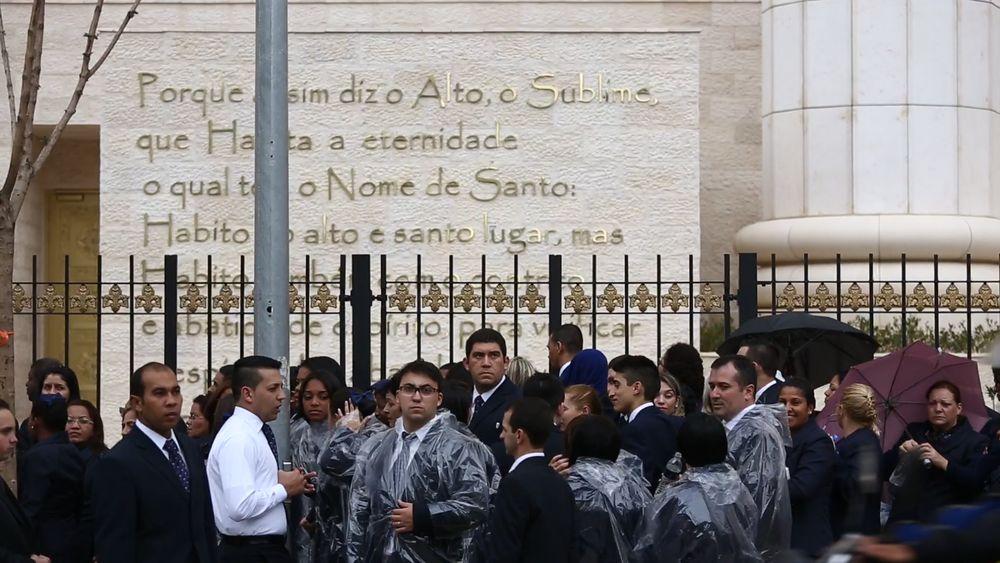 Obreiros se enfileiram na chuva enquanto esperam para entrar no templo (Carlos Cecconello/Folhapress)